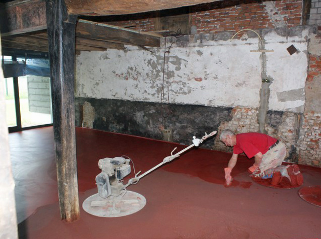 Volledig gekleurde osserode bloed gepleisterde cementdekvloer in een boederij.