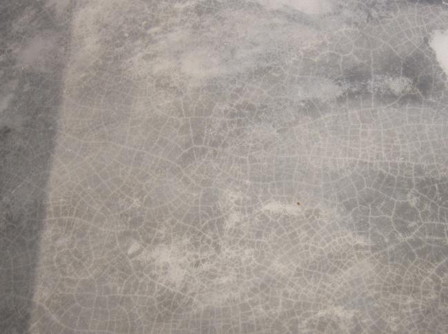 Craquelé (soort spinnenwebben) in de gepleisterde cementdekvloer. Het is mogelijk dat er craquelé ontstaat in een gepleisterde cementdekvloer doordat er gewerkt wordt met natuurlijke materialen.